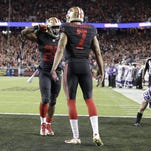 San Francisco 49ers running back Carlos Hyde, left, celebrates after running for a 10-yard touchdown with quarterback Colin Kaepernick (7) during the first half of an NFL football game against the Minnesota Vikings on Monday.