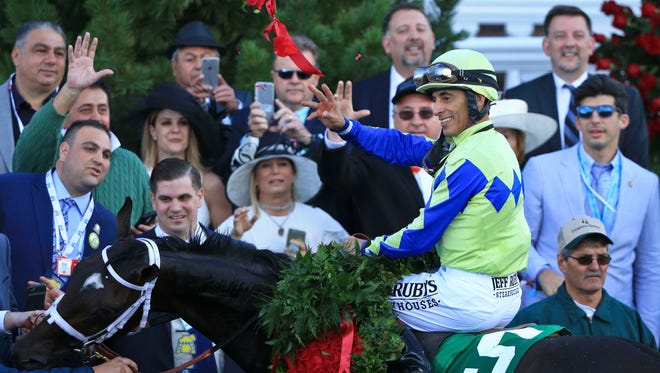 Jockey John Velazquez throws roses atop Always Dreaming after winning the 143rd Kentucky Derby Saturday at Churchill Downs.