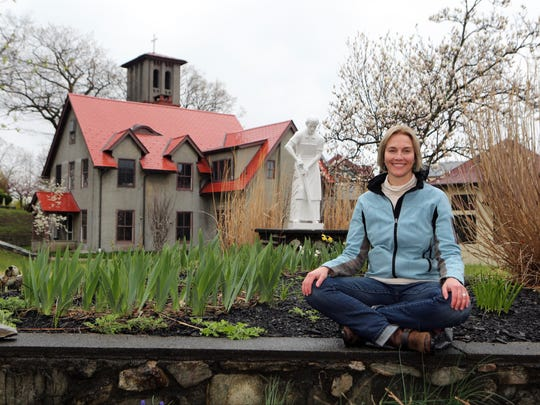 Amy Reyer, who leads meditation classes at the Graymoor Spiritual Life Center in Garrison, is pictured with the historic St. Francis Chapel on the property April 25, 2017.
