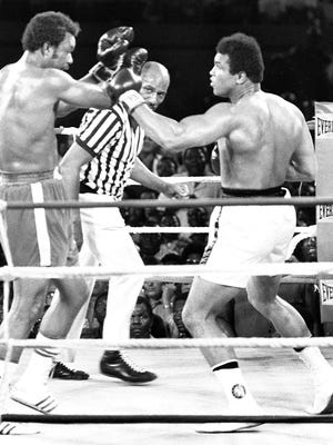 Taking back the title, Ali (right) knocks out George Foreman in 1974 in one of his greatest victories.