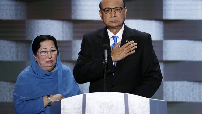 In this July 28, 2016, photo, Khizr Khan, father of fallen Army Capt. Humayun Khan and his wife Ghazala speak during the final day of the Democratic National Convention in Philadelphia.