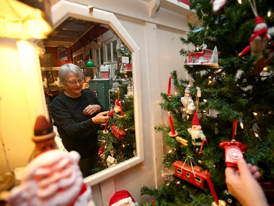 Carolee Pederson is reflected in a mirror as she adjusts the ornaments on one of the many trees at The Christmas House in the Port Madison area of Bainbridge Island.