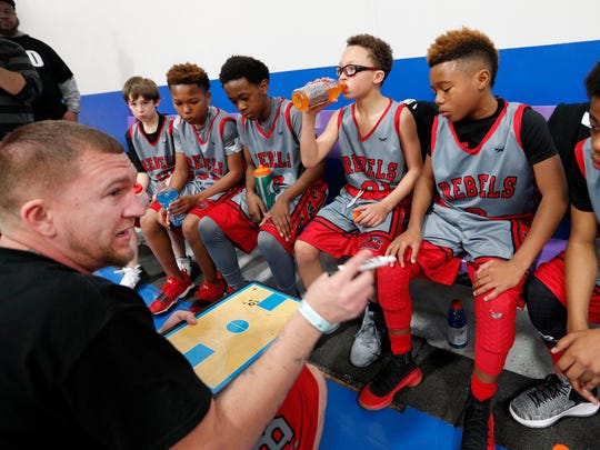 Christopher McLavish coaches his Flint Town Elite team as they play OH Dose, from Ohio at the Best Choice Fieldhouse in Fishers. Josh Helvie, Midwest Circuit AAU organizer,  began a drive to collect bottles of drinking water for The Flint Town Elite, from Flint Mi., 5th grade boys basketball team on Saturday April 21, 2018. The steady stream of people donating water has been nonstop. Two moving trucks and a semi trailer are nearly full of drinking water for the people of Flint.