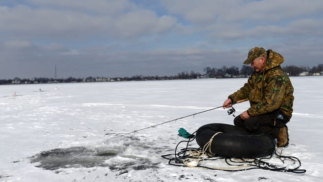 Steve Leonard, from Columbus, kneels down as he fishes Thursday, Jan. 21, 2016, off of Fairfield Beach on Buckeye Lake. Leonard was fishing with Todd Leonard, from Columbus and Luke Francis, from Grove City on the four to five inches of ice that have formed on lake over the last few days of sub-freezing temperatures.