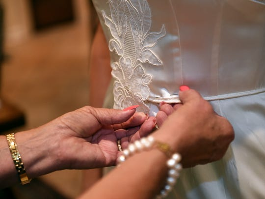 Sandra Ashford makes an alteration Tuesday at her home in Ridgeland to Christina Smith's grandmother's wedding dress, which Smith will wear next month in her wedding. Ashford specializes in altering and customizing family heirloom wedding dresses.