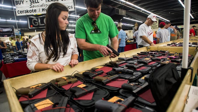Jena Morel and her fiancé Kevin Latiolais shop through a handgun booth during the Louisiana Gun & Knife Show at the Lafayette Event Center in Lafayette, Saturday, Aug. 8, 2015.