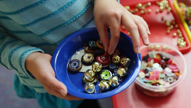 Elizabeth Hirsch, 8, picks out buttons, bells, bottle caps and other items to make a wind chime with during the Creative Kids After-School Adventures class at the Salem Public Library. Future Adventures classes will be Oct. 13, Nov. 17 and Dec. 15.