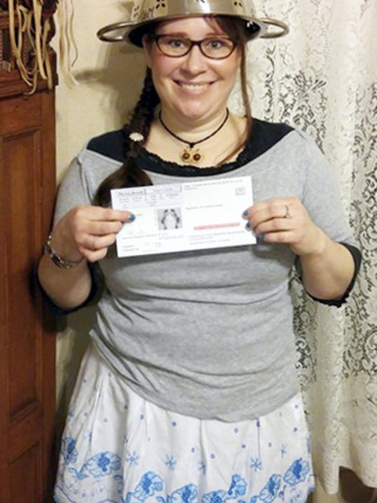 "In this Nov. 12, 2015 photo provided by Darrick Fauvel, Lindsay Miller of Lowell, Mass., wears a spaghetti strainer to reflect her religious beliefs while holding her temporary driver license that also bears a photo of her wearing the colander. Miller said she ""absolutely loves the history and the story"" of pastafarians, who are part of the Church of the Flying Spaghetti Monster. The Massachusetts Registry of Motor Vehicles initially forbade Miller to wear the colander in the identification photo. She said the agency reversed the decision and apologized. (Darrick Fauvel via AP)"