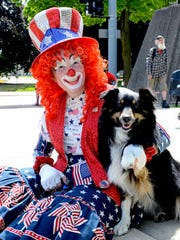 """Laura """"Dustee"""" Sorrell and her dog Sophie, an Australian shepherd, watch the Lansing Fourth of July parade go by Monday in downtown Lansing."""
