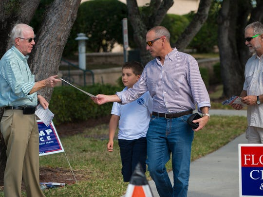 Mike Barnes, left, a Democratic volunteer, hands a sample ballot to Edward Kaufman, who brought his son Herman along as he went to vote at the St. Ann's Jubilee Center in Naples on Tuesday, Nov. 8, 2016. On the right is Republican volunteer Rick Lussy.