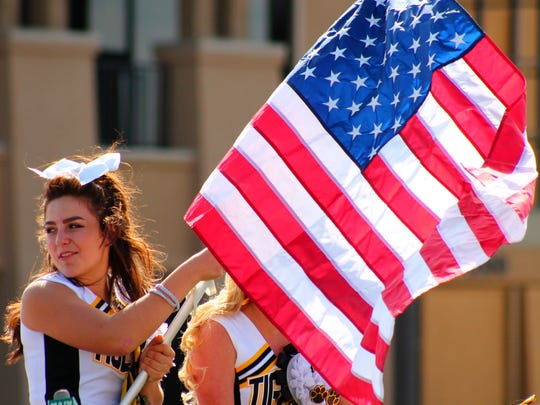 An Alamogordo High School cheerleader waves the American flag while the Alamogordo High School homecoming parade proceeded west on Tenth Street on Friday afternoon. The Tigers trounced Deming 56-12 in the homecoming game. Alamogordo is now 6-0.