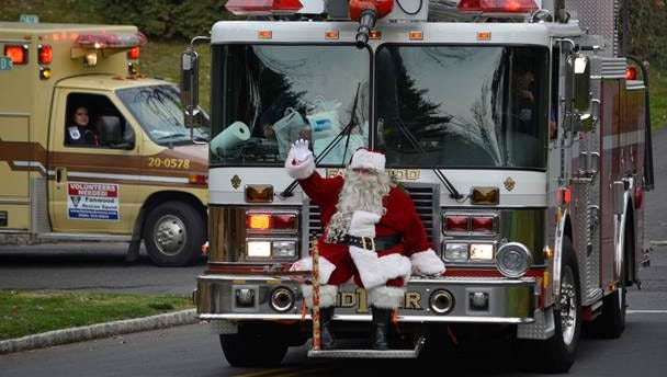 Riding aboard the Fanwood Fire Dept.'s Ladder One, and accompanied by the Rescue Squad, Santa turns down a street to deliver presents in Fanwood, NJ, Saturday, Dec. 12, 2015.