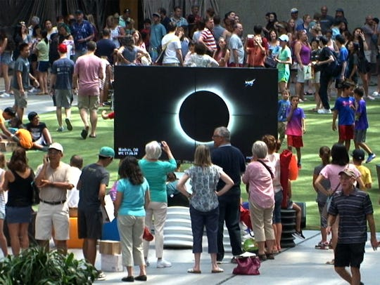 People wait in line for solar glasses at Bell Works