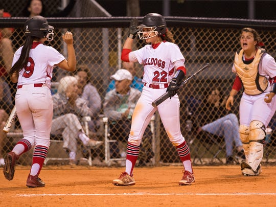 South Fork's Katelyn Aguirre (left) is congratulated by teammate Malea Rolle after scoring on a ground ball hit by teammate Maddie Kelleher, tying the game at 1 against Olympic Heights during sixth inning of the Region 4-7A quarterfinal high school softball game Wednesday, May 2, 2018, at South Fork High School in Tropical Farms.
