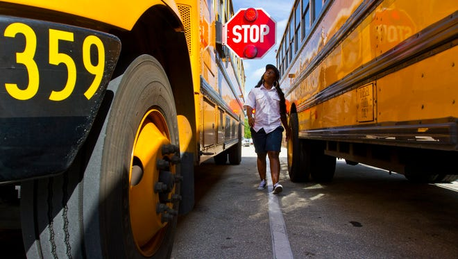 Tavarsha Hamilton, of Fort Myers, a school bus driver for the Lee County School District, does her preliminary lights and safety vehicle check prior to the start of her route Monday, November 16, 2015.