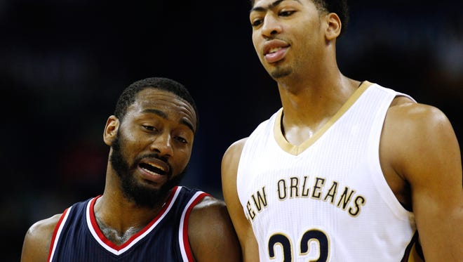 Washington Wizards guard John Wall, left, and New Orleans Pelicans forward Anthony Davis talk to each other during the first half of an NBA basketball game, Monday, Jan. 5, 2015, in New Orleans. (AP Photo/Jonathan Bachman)
