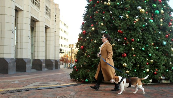 """Kristie Murry walks her 8-year-old Beagle """"Jackson"""" past the 30-foot Christmas tree in downtown Memphis when the weather was still cold."""