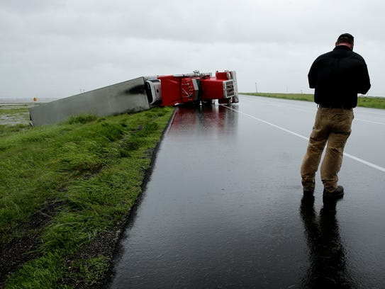 A passing motorist stops to look at a flipped truck