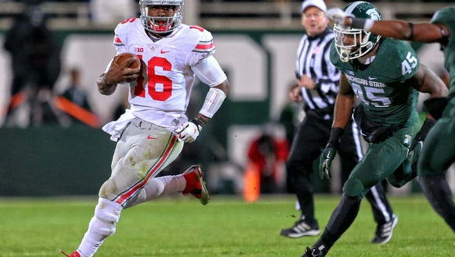 Ohio State quarterback J.T. Barrett (16) gets outside of Michigan State linebacker Darien Harris (45) during the second half Saturday night at Spartan Stadium.