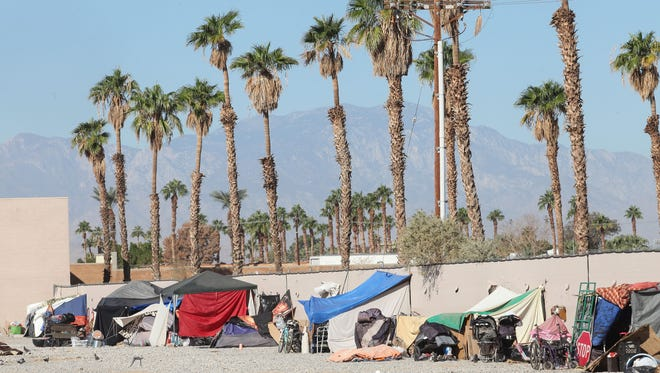 Dozens of tents and makeshift shelters line a fence in a large vacant lot in Indio.