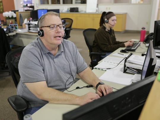 Collections specialist Jim Coenen talks to a client at Americollect Feb. 16 in Manitowoc.