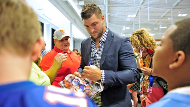 Former Florida Gators quarterback Tim Tebow signs autographs for fans after speaking at the Music City Sports Festival on Saturday at Music City Center.