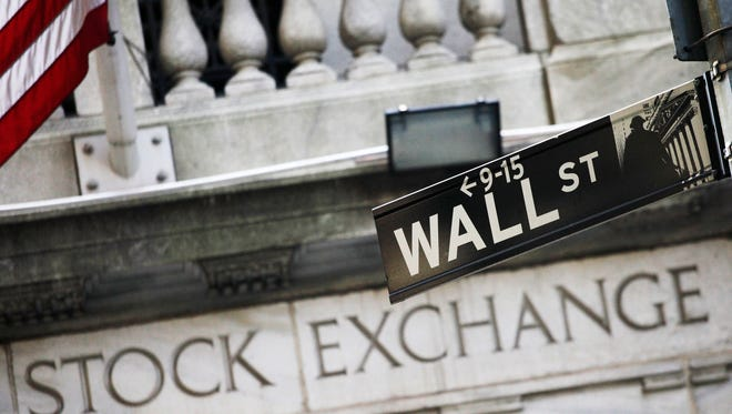This July 16, 2013, file photo shows a street sign for Wall Street outside the New York Stock Exchange.