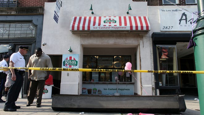 Investigators look over the debris of a fallen security door outside a Rita's Water Ice store in the Brewerytown section of Philadelphia on June 28.