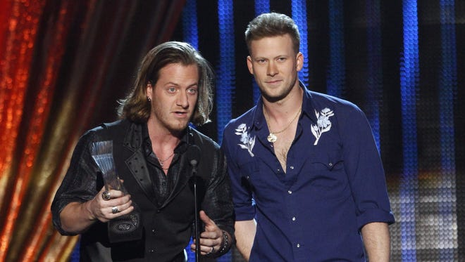 """Tyler Hubbard, left, and Brian Kelley of Florida Georgia Line accept their award at CMT Artists of the Year""""  on , Dec. 3, 2013."""