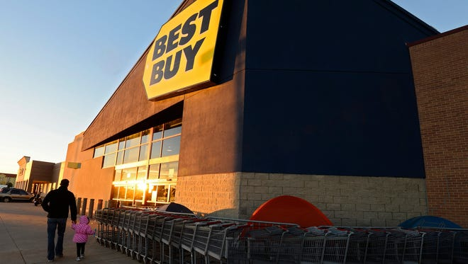 People walk into a Best Buy past people camping out in tents in Dallas on Wednesday.