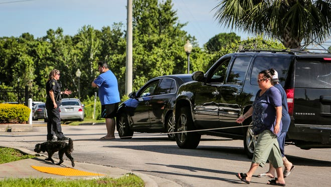 An Orlando Police officer checks the ID of residents trying to enter the Westbrook Apartments in Orlando, Fla., on Tuesday, June 12, 2018. Four young children were discovered dead at the west Orlando apartment complex late Monday, about 21 hours after a standoff that began when an Orlando police officer was shot responding to a domestic violence call. (Jacob Langston