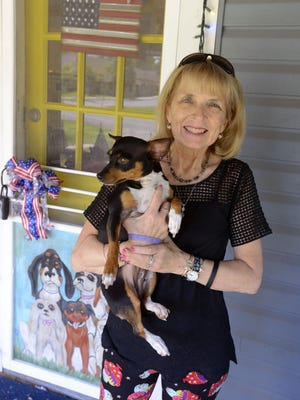 Pam Bell, owner of Hotel for Dogs and Cats Adoption Center, holds a newly adopted dog Sunday, June 18, 2017 at the Hotel for Dogs and Cats Adoption Center. The center just celebrated its eighth anniversary.