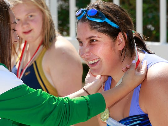 Crystal Ramos, of Rio Rancho, receives a gold medal for competing in the 25-meter freestyle race during Special Olympics New Mexico's Four Corners Invitational on Saturday at the Farmington Aquatic Center.