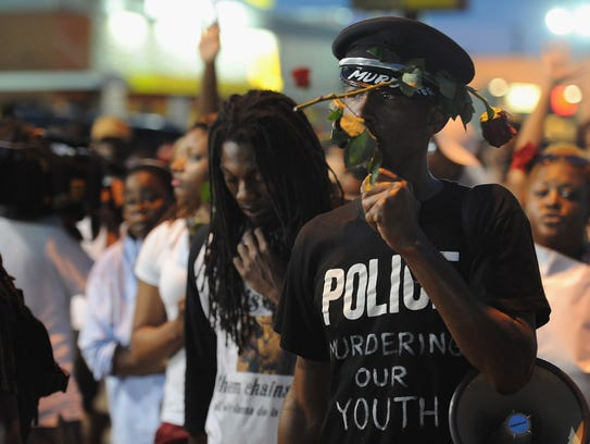 Demonstrators take part in a protest in Ferguson, Missouri on August 18, 2014. Police fired tear gas in another night of unrest in a Missouri town where a white police officer shot and killed an unarmed black teenager, just hours after President Barack Obama called for calm. AFP PHOTO / Michael B. ThomasMichael B. Thomas/AFP/Getty Images