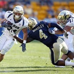 Akron Zips running back Conor Hundley (34) rushes the ball past Pittsburgh Panthers linebacker Bam Bradley (4) during the fourth quarter at Heinz Field in September of 2014.