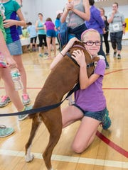 Opal gives a hug to Maggie Ryan, 11, of Colchester before the start of the annual VNA's Vermont Respite House 5K Fun Run & Jiggety Jog.