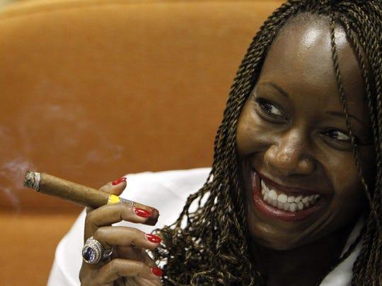 A woman posses while smoking a cigar at the Habano
