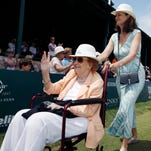 Nancy Jeffett, left, waves to the crowd as she is wheeled by Pam Shriver, center, after being inducted into the International Tennis Hall of Fame
