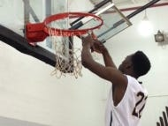 Javan Thomas (No. 22) takes his turn cutting down the basketball net after Schoolcraft College's men's basketball team won the MCCAA title Saturday.
