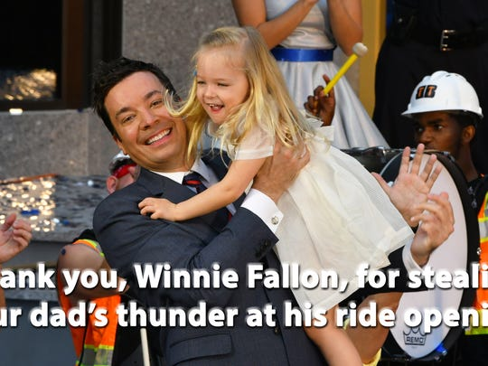 Jimmy Fallon holds up his daughter, Winnie Rose, at the grand opening of Race Through New York Starring Jimmy Fallon at Universal Orlando. 3-year-old Winnie was dancing up a storm on the stage, earning major cheers from the crowd.