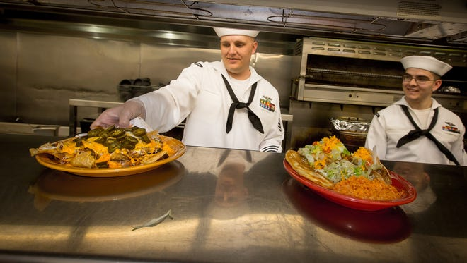 Culinary Specialist First Class Charles Johnson, left, and Culinary Specialist Third Class Jordan Prince serve up meals at La Posta de Mesilla, April 21, 2016. Johnson and Prince, who are both cooks on the submarine USS New Mexico, were there to learn the recipes and cooking techniques of the restaurant so they can utilize them while feeding the 130 sailors onboard.