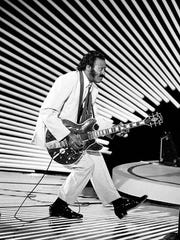 """In 1955, Chuck Berry recorded his first single, """"Maybellene,"""" for Chess Records in Chicago. Here, Chuck Berry performs his """"duck walk"""" on stage as he plays his guitar on April 4, 1980."""