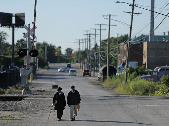 Two residents of the Delray neighborhood in Detroit walk back to their home through an industrial part of the neighborhood on Wednesday, July 15, 2015.