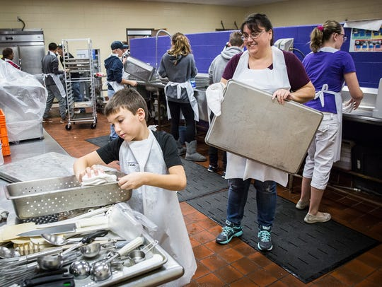 Volunteers wash trays for guests during the annual