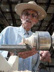 Phil Johnson of Mansfield makes a wooden top during a past Ohio Heritage Days at Malabar Farm. Molyet/News Journal
