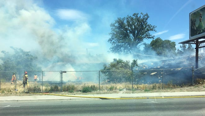 Reno firefighters put out a brush fire that sparked in a vacant lot near South Wells Avenue and Stewart Street on June 6, 2017. The fire was burning between two buildings and burned through a quarter of an acre of cheatgrass.