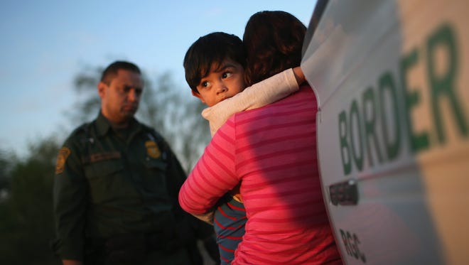 Salvadoran boy clings to his mother after she turned themselves in to U.S. Border Patrol agents near Rio Grande City, Texas.
