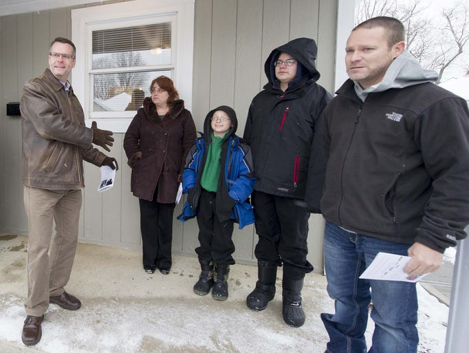 Jim Morris, president and CEO of Habitat for Humanity, left, dedicates the refurbished home to Paula Weifenbach who stands with her two sons, Alex, 10, and Evan, 13. Construction Project Coordinator Matt Trulock, right, kept the refurbish project on schedule. Habitat for Humanity of Greater Indianapolis dedicated its first home in Hendricks County Friday, December 6, 2013. The Danville home was refurbished for the Paula Weifenbach and her two sons - Evan, 13, and Alex, 10.
