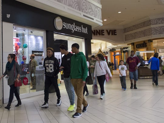 Shoppers walk through the Acadiana Mall in December