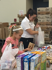 Savannah Clements and Angela Smith pack food items for Grace Packs.